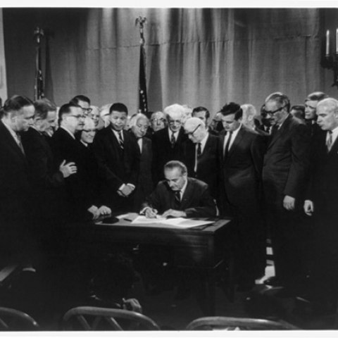 President Lyndon Johnson signing the Fair Housing Act, 1968, surrounded by onlookers