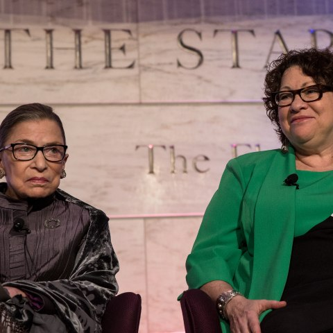 Two women on stage, one in green and one in dark grey