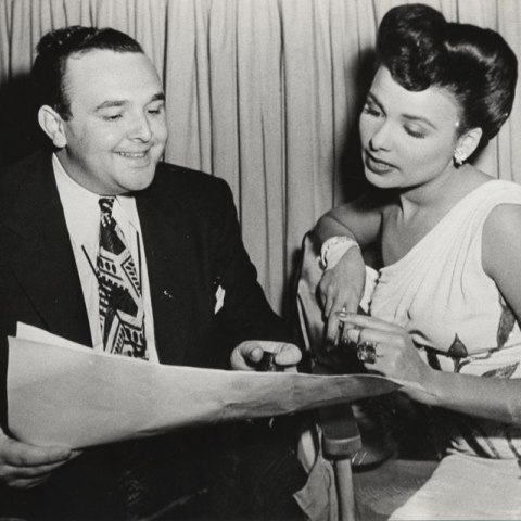 Black and white photo of a man and woman looking at pages of paper.