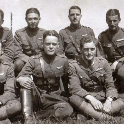 Soldier sits posed in grass with fellow soldiers, wearing uniform and looking at camera