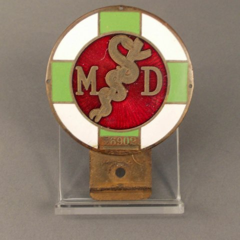 An object that is a circle with alternating white and green bands. In the middle is a red circle with M&D and the universal medical sign in it. There is a bronze-colored part sticking out of the bottom with a hole in it.