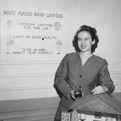 "Black and white photo of woman smiling in front of sign that says ""What makes good lighting"" and a model of a house"