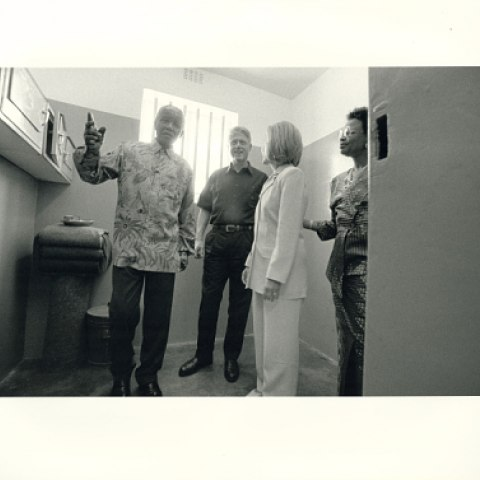Black and white photo of our people standing in a small room. Nelson Mandela gestures. President Clinton looks with a half smile. Hillary Clinton shown in profile. Woman looks in through the door.