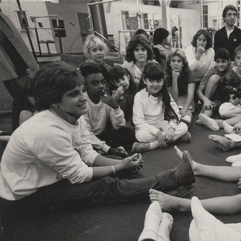 Olympic gymnast Mary Lou Retton sits on a mat in a gym circled by children of various ages. She appears to be midsentence answering a question from a youth in front of her.