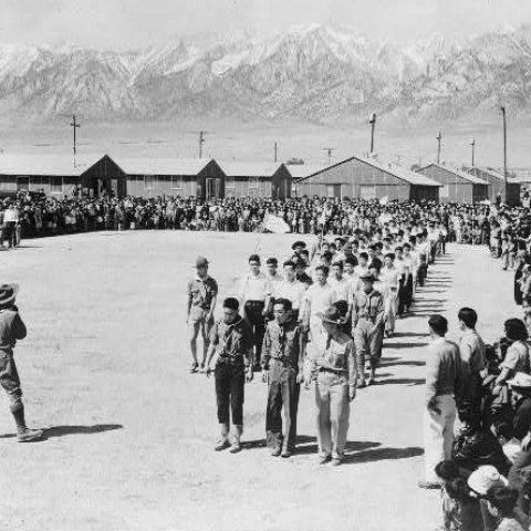 (Detail) Black and white photo of gathering in center of camp with buildings in background. Boy Scouts line up while community watches. In background, high mountains with snow on top.