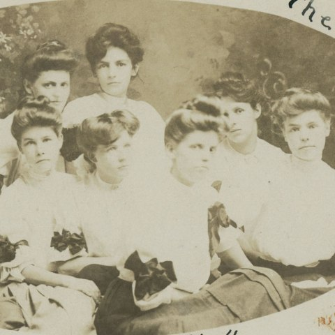 Black and white posed photo of women, each with their hair piled on top of their head and high-collared blouses.