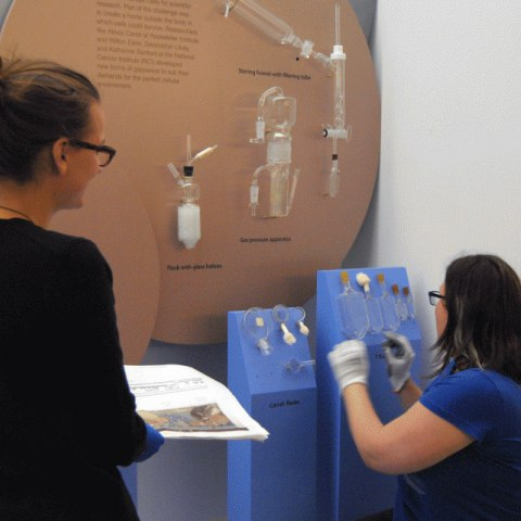One woman kneels into a display case, placing glass objects onto a blue platform/display armature. Another woman holds design plans on paper and watches. In background, case is open to show objects and text panels.
