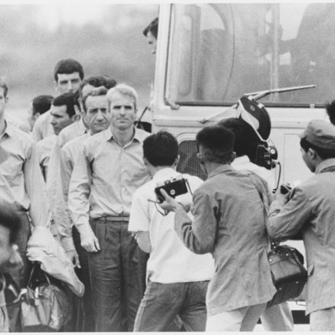 John McCain and other returning soldiers stand before a crowd