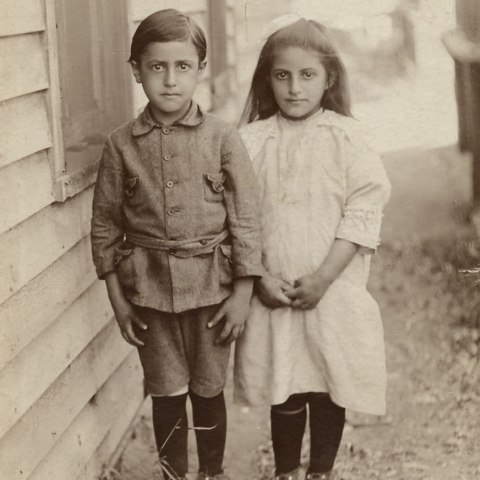 A pair of children in period clothing stand next to a clapboard house