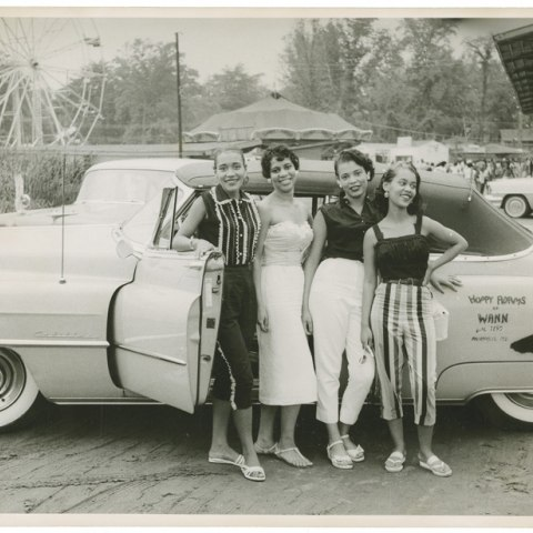 Photograph, circa 1958, of four young African American women standing beside a convertible automobile