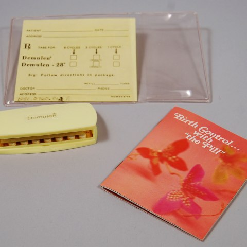 Pink brochure with butterflies on the cover, pack of pills, and document