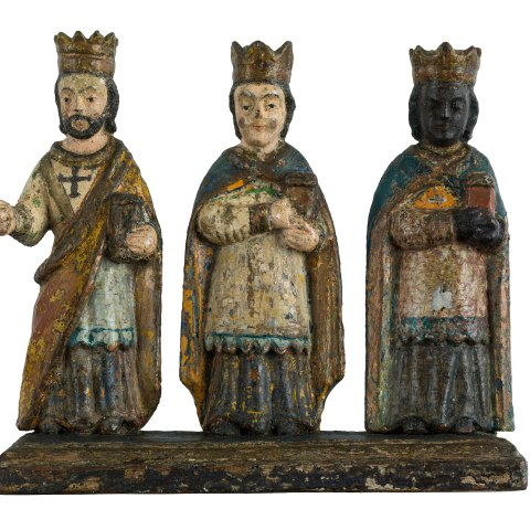 Three statuettes of kings complete with robes and gowns stand on the same base.