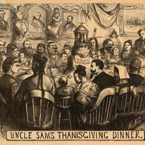 """Cartoon shows a large group of men and women from of various races, ethnicities, and  cultural backgrounds gathered around a table for a meal. At the head of the table, Uncle Sam carves a turkey; the table's center is dominated by the model of a temple with the words """"Universal Suffrage."""""""