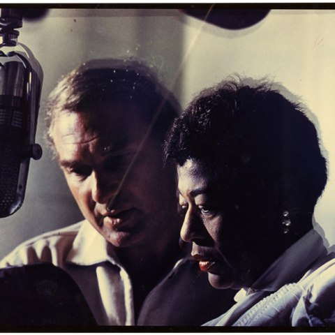 Norman Granz and Ella Fitzgerald stand side-by-side in front of a microphone