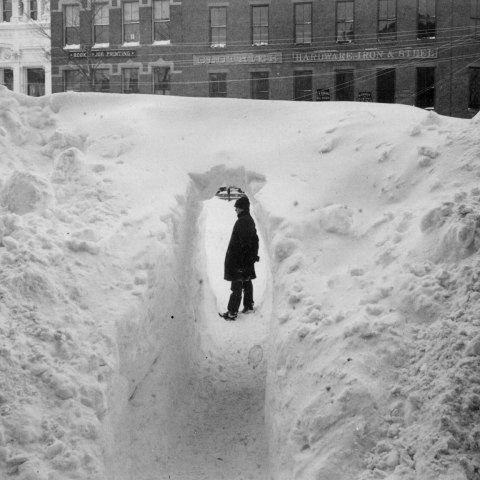 """Black and white photo of a large bank of snow. In the center, a tunnel has been made. A man stands inside the tunnel. Behind him, five buildings over one story high. """"Hardware Iron & Steel"""" says the sign on one."""