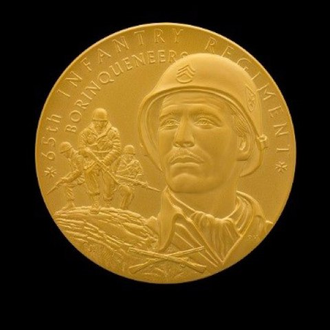 Gold medal with portrait of a man's face. He wears a helmet and stares past the viewer. Behind him, other soldiers in uniforms and helmets hold guns in a tactical position.