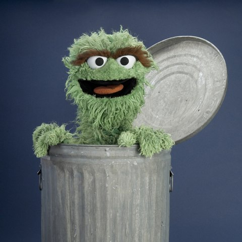 Photo of Oscar the Grouch puppet (green with big eyes, scraggly fur) popping out of an aluminum garbage can