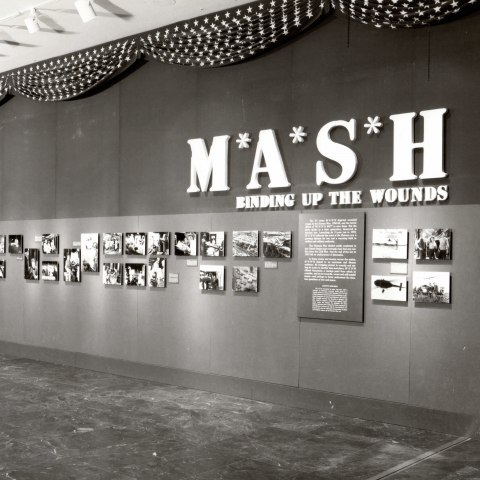 A black and white photograph of a wall inside a building covered in a line of photographs with text panels and large lettering.