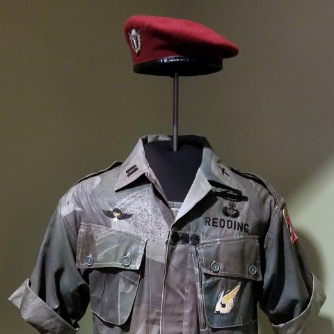Green and brown military uniform with red beret. Owner's name, Redding, written on left breast