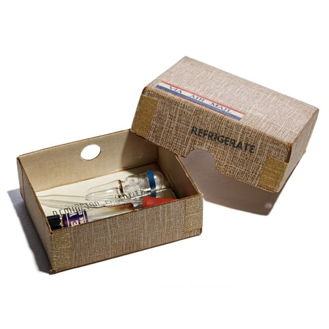 """An open brown box. The top of the box has a label reading """"via air mail"""" and a stamp that says refrigerate, but no other markings. Insides the open box, there is a pipette and other components of the pregnancy test."""