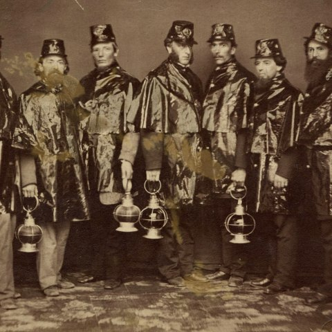 Black and white photo of seven men. Each carries a lander with a circular handle and wears a matching hat and cape-like uniform in shiny fabric. They face the camera.