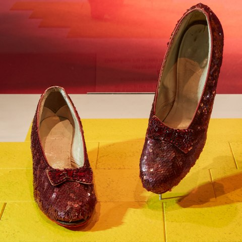 Pair of red shoes with sequins with yellow brick background