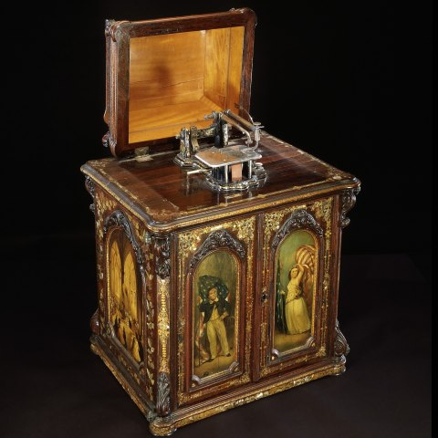 A full-length photo of the sewing machine. It looks like a box with painted doors featuring images of a man and woman. The top is open to show the sewing needle.