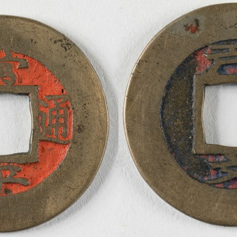 A round coin with a square removed from the center. One side is marked with the color orange.