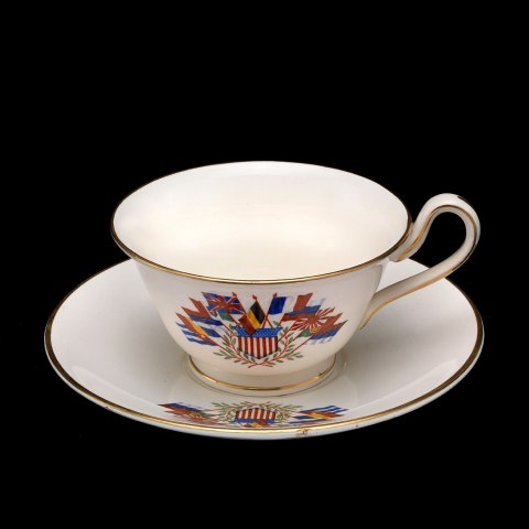 A white china teacup and saucer sit against a black background. The saucer and the cup have different European flags and the US flag on them, and all of the edges are lined with gold