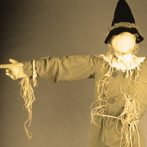 Costume on a faceless manikin includes pointed black hat tied with brown ribbon, white collar, burlap outfit, and hay pieces dangling.