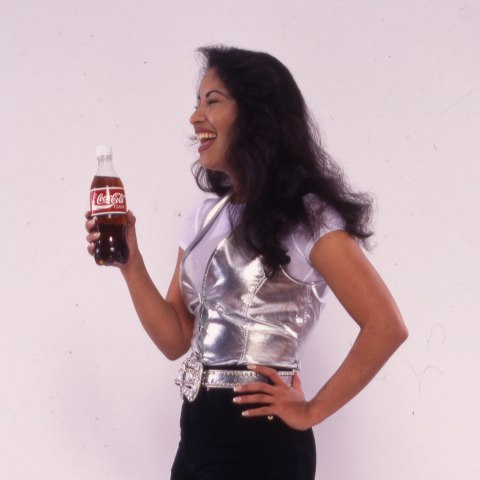 Selena laughs and holds a Coke. She wears a silver vest, white t-shirt, and black pants.