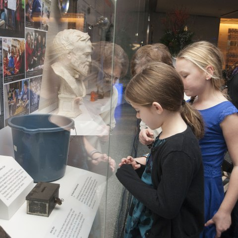 Two young girls look through the glass of a museum display to gaze at a blue bucket among other objects like a pair of boots or a bust of a man.