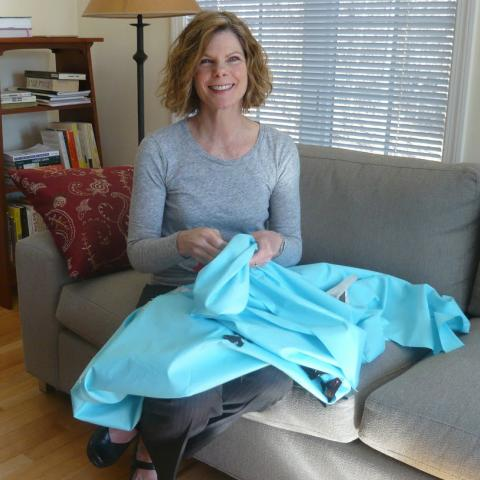 Woman sitting on couch with turquoise fabric in her lap, holding some of its folds. Smiling. Gray couch, bookshelf in background.