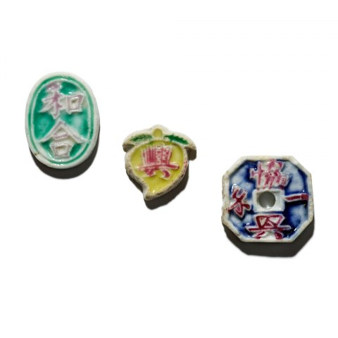 Three small, colorful tokens--appear to be glass. Oval one is turquoise. Yellow one is lemon-shaped. Blue one is a rounded square. All have characters on them.