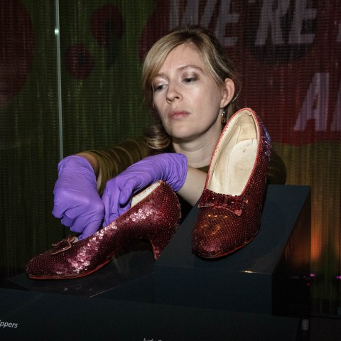 Woman wearing purple latex gloves presses gently into the inside of one of the Ruby Slippers into a case.
