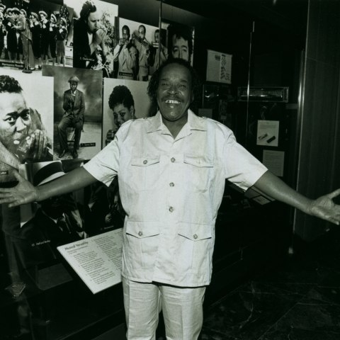 A photograph of a smiling man, his arms outstretched, in front of an exhibit with images on the wall, objects against it, and signs with captions on them.
