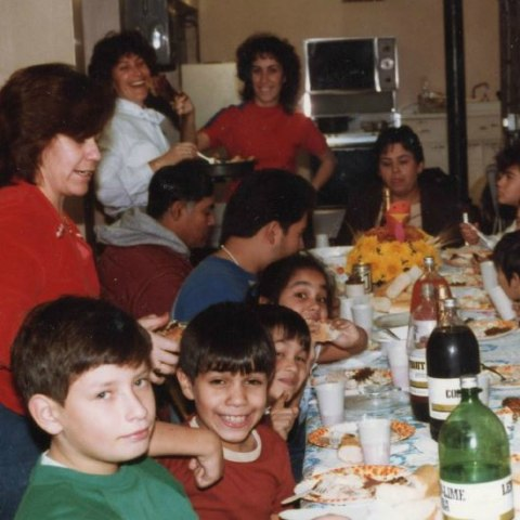 Family members gather around a Thanksgiving table and smile.