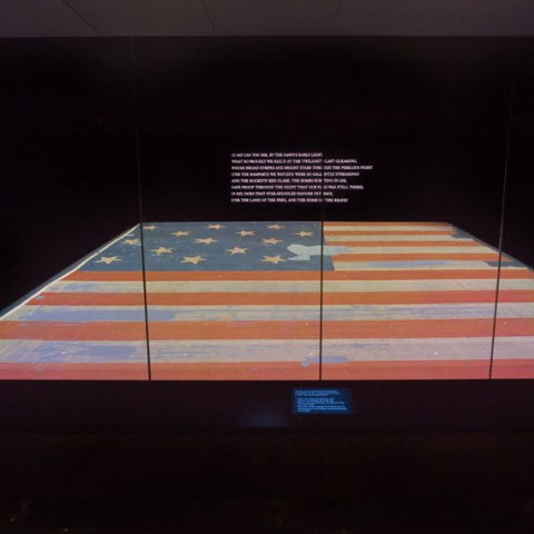 Star-Spangled Banner flag on a platform, nearly horizontal. Dark room. The flag is battered but vivid. On the wall, the first stanza of national anthem in white.