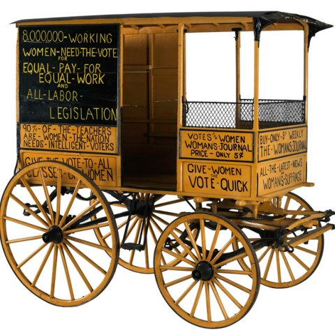 a 4-wheeled, covered wagon with messages of suffrage and equal rights painted on the side