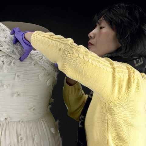 A woman wearing a yellow sweater and wearing purple gloves carefully manipulates the fabric of a beautiful white gown with delicate flower and sequin details. The gown is one-shoulder strap. It was worn by First Lady Michelle Obama. The dress is on a form.