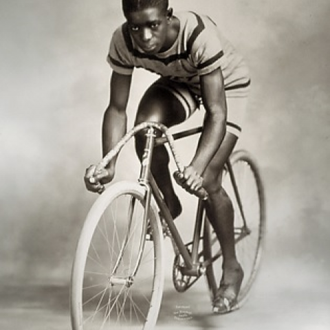 Young man posing on a bike with low handle bars. He wears short shorts and t-shirt with stripes, perhaps racing clothes. He is African American.