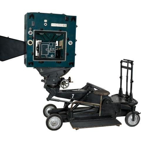 Technicolor camera with large lens, camera casing, and four wheels