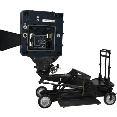 Movie camera in large apparatus with four small wheels.