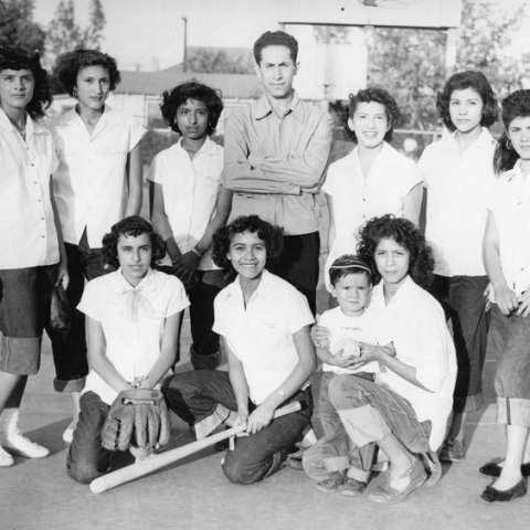 A group of young women in white, button up, short sleeved shirts stands and kneels for the photograph. In the middle of the back row there is a man with a serious expression. The young woman kneeling in the center is holding a baseball bat.