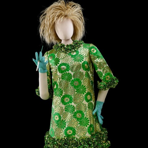 A mannequin wears a blonde, spiky wig and a lacquered shift dress with green and gold daisies. The bottom hem, neckline, and sleeves are ruffled with teal, wrist-length gloves and a cigarette holder. Her shoes are green ankle-high booties with low heels and gold details.