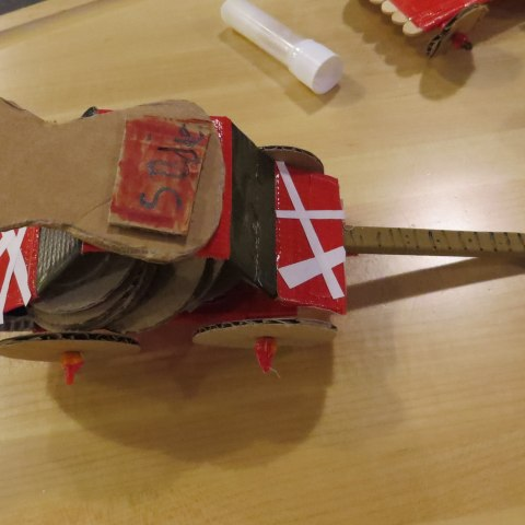 Small, handmade car designed from cardboard pieces in red, white, and brown.