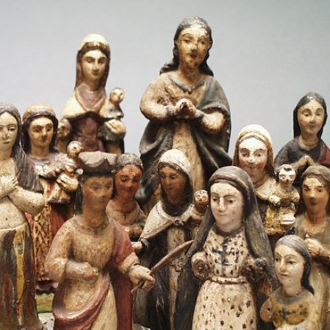 Group of small wooden carved figures, some with painted details.