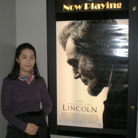 """Woman in purple sweater standing beside """"Now Playing"""" poster for """"Lincoln"""" movie, smiling."""
