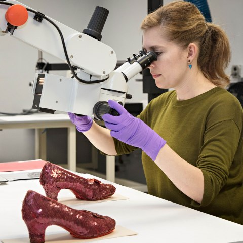 Woman in green shirt with purple latex gloves adjusts a microscope. She is looking at the Ruby Slippers.