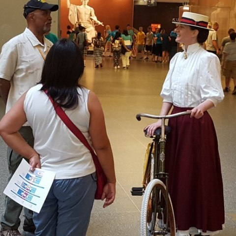 A woman in a historical outfit (high collared white shirt with elbow-length sleeves, long burgundy skirt, boater hat) and a bike speaks to two museum visitors
